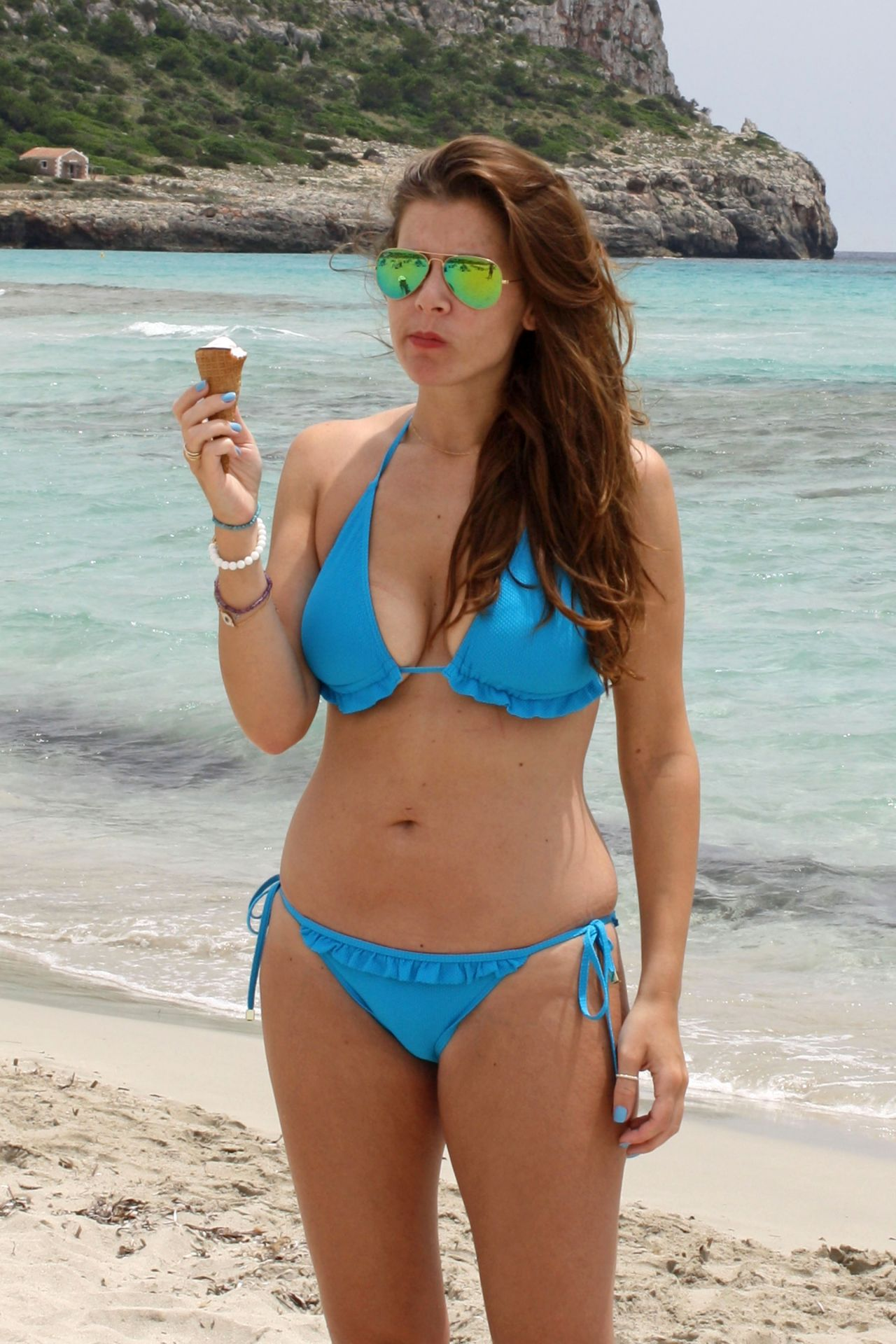 Imogen Thomas in a Blue Bikini - Eating a Ice Cream on a beach in Spain - June 2014